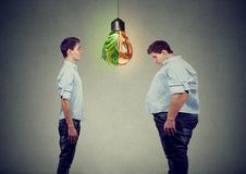 Νέο ευτυχές λεπτό άτομο που εξετάζει το λυπημένο παχύ τύπο ο ίδιος Σωστή έννοια διατροφής επιλογής διατροφής στοκ εικόνες με δικαίωμα ελεύθερης χρήσης