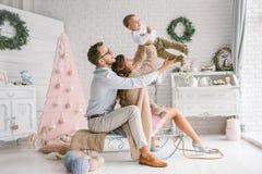 Νέο ευτυχές μωρό οικογενειακής εκμετάλλευσης στο στούντιο ντεκόρ Χριστουγέννων στοκ φωτογραφία