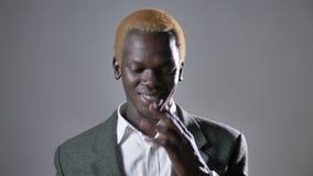 Νέο ευτυχές ξανθό αφρικανικό άτομο που χαμογελά στη κάμερα και σχετικά με το πρόσωπο, που απομονώνονται στο γκρίζο υπόβαθρο, τον  απόθεμα βίντεο