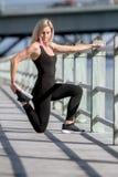 Νέο ευτυχές ξανθό κορίτσι που κάνει τον αθλητισμό στην πόλη στοκ φωτογραφία