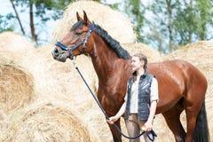 Νέο εφηβικό κορίτσι ιδιοκτητών που οδηγεί το όμορφο άλογο κάστανων Στοκ Φωτογραφίες