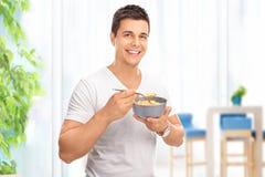 Νέο εύθυμο άτομο που τρώει τα δημητριακά από ένα κύπελλο Στοκ εικόνα με δικαίωμα ελεύθερης χρήσης
