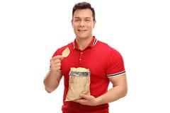 Νέο εύθυμο άτομο που τρώει τα τσιπ πατατών Στοκ εικόνες με δικαίωμα ελεύθερης χρήσης