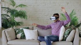 Νέο εύθυμο άτομο που φορά την κάσκα εικονικής πραγματικότητας που έχει την τηλεοπτική εμπειρία 360 VR καθμένος στον καναπέ στο κα φιλμ μικρού μήκους