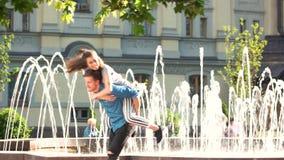 Νέο εύθυμο ζεύγος που έχει τη διασκέδαση κοντά στην πηγή πόλεων απόθεμα βίντεο