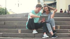 Νέο εύθυμο ζεύγος που χρησιμοποιεί την ψηφιακή ταμπλέτα υπαίθρια απόθεμα βίντεο