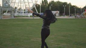 Νέο εύθυμο κορίτσι στο ηλιόλουστο θερινό πάρκο που ανοίγει τα χέρια της στις πλευρές περπατώντας στο πάρκο φιλμ μικρού μήκους