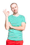 Νέο εύθυμο χαμογελώντας άτομο με την εντάξει χειρονομία στη ριγωτή άσπρη και τυρκουάζ μπλούζα και τα πορτοκαλιά τζιν που απομονώνο Στοκ φωτογραφίες με δικαίωμα ελεύθερης χρήσης