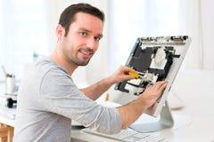 Νέο ελκυστικό άτομο που επισκευάζει έναν υπολογιστή Στοκ Φωτογραφίες