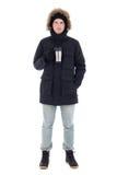 Νέο ελκυστικό άτομο στο μαύρο χειμερινό σακάκι με την κούπα του καφέ ι Στοκ φωτογραφία με δικαίωμα ελεύθερης χρήσης