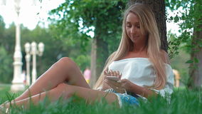 Νέο ελκυστικό κορίτσι που χρησιμοποιεί το smartphone καθμένος στο πάρκο, αποτελέσματα φλογών φιλμ μικρού μήκους