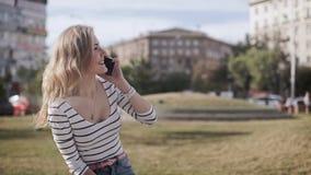 Νέο ελκυστικό κορίτσι σε ένα πάρκο πόλεων με ένα τηλέφωνο σε μια θερινή ημέρα απόθεμα βίντεο