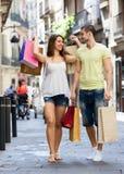 Νέο ζευγάρι χαμόγελου με το πακέτο αγορών στην πόλη Στοκ Εικόνες