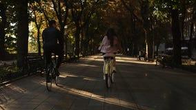 Νέο ζεύγος - άνδρας στα μαύρα περιστασιακά ενδύματα και γυναίκα στη ρόδινη μετάβαση να οδηγηθούν τα ποδήλατά τους στο πάρκο θεριν απόθεμα βίντεο