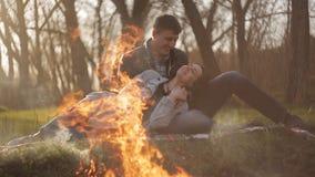 Νέο ζεύγος ερωτευμένο κατά μια ημερομηνία από την πυρκαγιά Ένας τύπος αγκαλιάζει μια συνεδρίαση κοριτσιών σε μια κουβέρτα από την απόθεμα βίντεο