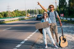 νέο ζεύγος ερωτευμένο με το κενό χαρτόνι που κάνει ωτοστόπ ενώ Στοκ Εικόνες