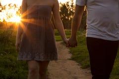 Νέο ζεύγος ερωτευμένο σε έναν τομέα με τον ήλιο μέσω των δέντρων στοκ εικόνες