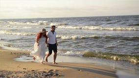 Νέο ζεύγος ερωτευμένο στην παραλία τα όμορφα ενδύματα συνδέο&up Χέρια και αγκάλιασμα εκμετάλλευσης εραστών φιλμ μικρού μήκους