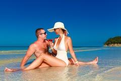 Νέο ζεύγος ερωτευμένο στην τροπική παραλία και απόλαυση του κοκτέιλ Στοκ Εικόνα