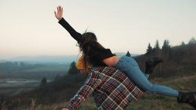 Νέο ζεύγος ερωτευμένο στις διακοπές που απολαμβάνουν τα βουνά Το ελκυστικό άτομο φέρνει τη φίλη στους ώμους και τις περιστροφές τ απόθεμα βίντεο