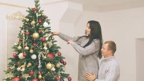 Νέο ζεύγος ερωτευμένο στο νέο ντεκόρ έτους με τα δώρα και το χριστουγεννιάτικο δέντρο, υπάρχει θόρυβος στο βίντεο φιλμ μικρού μήκους
