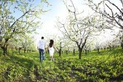 Νέο ζεύγος ερωτευμένο τρέχοντας την άνοιξη τον κήπο ανθών Στοκ Φωτογραφία