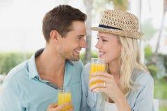Νέο ζεύγος ισχίων που πίνει το χυμό από πορτοκάλι από κοινού Στοκ εικόνες με δικαίωμα ελεύθερης χρήσης