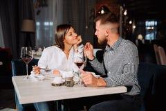 Νέο ζεύγος κατά μια ημερομηνία Ένας άνδρας ταΐζει στη γυναίκα του ένα εύγευστο επιδόρπιο Ζεύγος που γελά στο εστιατόριο στοκ φωτογραφία με δικαίωμα ελεύθερης χρήσης