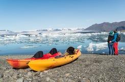 Νέο ζεύγος κοντά σε δύο καγιάκ στην ακτή μιας λίμνης παγετώνων Jokulsarlon Ισλανδία στοκ εικόνες