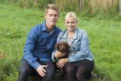 Νέο ζεύγος με ένα κουτάβι του Λαμπραντόρ Στοκ φωτογραφίες με δικαίωμα ελεύθερης χρήσης