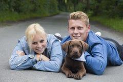 Νέο ζεύγος με ένα κουτάβι του Λαμπραντόρ Στοκ εικόνα με δικαίωμα ελεύθερης χρήσης