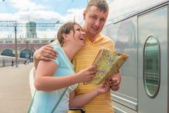 Νέο ζεύγος με διαθέσιμο κοντινό χαρτών το τραίνο Στοκ Εικόνες