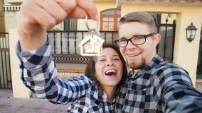 Νέο ζεύγος με τα κλειδιά που στέκονται έξω από το νέο σπίτι και που παίρνουν ένα selfie απόθεμα βίντεο