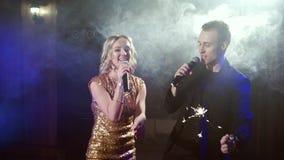 Νέο ζεύγος με τα sparklers που χορεύουν και που τραγουδούν σε ένα νυχτερινό κέντρο διασκέδασης απόθεμα βίντεο