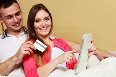 Νέο ζεύγος με την ταμπλέτα και την πιστωτική κάρτα στο σπίτι Στοκ Εικόνα