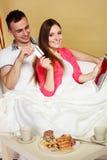 Νέο ζεύγος με την ταμπλέτα και την πιστωτική κάρτα στο σπίτι Στοκ Εικόνες