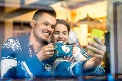 Νέο ζεύγος με τον καφέ στον καφέ το χειμώνα Στοκ φωτογραφία με δικαίωμα ελεύθερης χρήσης
