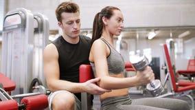 Νέο ζεύγος με τους μυς κάμψης αλτήρων στη γυμναστική απόθεμα βίντεο