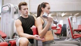 Νέο ζεύγος με τους μυς κάμψης αλτήρων στη γυμναστική φιλμ μικρού μήκους