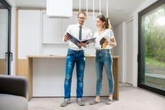 Νέο ζεύγος με το βιβλίο στο σύγχρονο εσωτερικό κουζινών Στοκ φωτογραφία με δικαίωμα ελεύθερης χρήσης