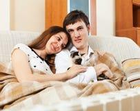Νέο ζεύγος με το γατάκι στον καναπέ στοκ φωτογραφία με δικαίωμα ελεύθερης χρήσης