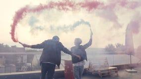 Νέο ζεύγος που έχει τη διασκέδαση με το χρωματισμένο καπνό στη στέγη του σύγχρονου κτηρίου Νέος τύπος με τη φίλη του που περπατά φιλμ μικρού μήκους