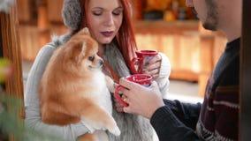 Νέο ζεύγος που έχει τη διασκέδαση υπαίθρια στο χρόνο Χριστουγέννων Πίνουν τα σκυλιά Cutie θερμαίνω-κρασιού και εκμετάλλευσης απόθεμα βίντεο
