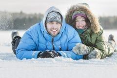 Νέο ζεύγος που έχει τη διασκέδαση που βρίσκεται υπαίθρια στο χιονώδες έδαφος που καλύπτει το χειμώνα χιονίζοντας ημέρα Στοκ Φωτογραφία