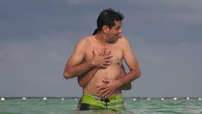Νέο ζεύγος που έχει τη διασκέδαση που κολυμπά στον ωκεανό απόθεμα βίντεο