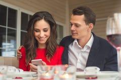 Νέο ζεύγος που έχει το ρομαντικό γεύμα στο εστιατόριο που χρησιμοποιεί το smartphone από κοινού στοκ φωτογραφία