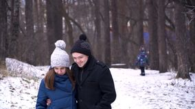 Νέο ζεύγος που αγκαλιάζει και που φιλά στο πάρκο το χειμώνα Πορτρέτο ενός όμορφου ζεύγους που ντύνεται στα χειμερινά ενδύματα στοκ φωτογραφίες