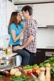 Νέο ζεύγος που αγκαλιάζει στην κουζίνα Στοκ εικόνες με δικαίωμα ελεύθερης χρήσης