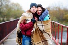 Νέο ζεύγος που αγκαλιάζεται, στεμένος στη γέφυρα, που καλύπτεται με το plai Στοκ Φωτογραφία