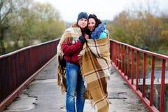 Νέο ζεύγος που αγκαλιάζεται, στεμένος στη γέφυρα, που καλύπτεται με το plai Στοκ φωτογραφία με δικαίωμα ελεύθερης χρήσης